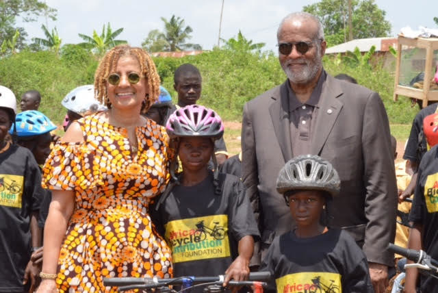 ABCF Executive Director Patricia Marshall Harris (left) and board chair A.Bruce Crawley (right) are shown, post-bike distribution ceremony, in Ejisu, Ashanti Region, Ghana with two helmeted bamboo bike recipients.