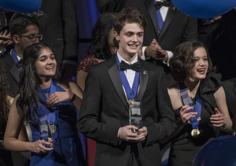 Washington, D.C., March 13, 2018—Benjy Firester (center), 18, of New York City, won first place and $250,000 in Regeneron Science Talent Search 2018, founded and produced by Society for Science & the Public. Isani Singh (left), 18, of Aurora, Colorado, was awarded third place and $150,000, and Natalia Orlovsky (right), 18, of Chadds Ford, Pennsylvania, was awarded second place and $175,000. Photo Credit: Chris Ayers/Society for Science & the Public