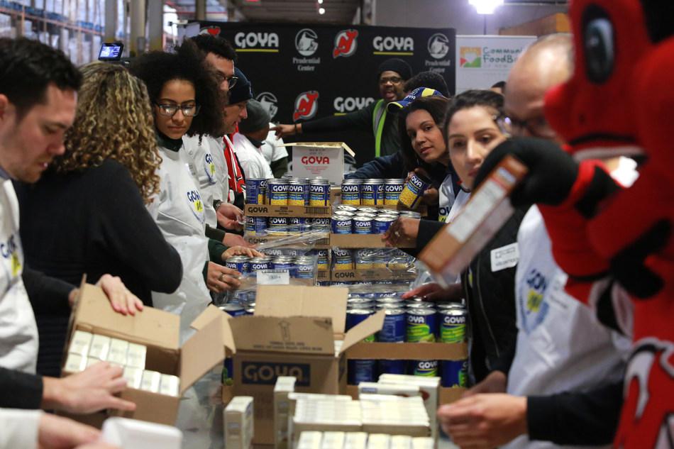 Goya, los New Jersey Devils y empleados de Prudential Center, junto con ex miembros de los Devils, ofrecieron tiempo voluntario para clasificar y empaquetar una parte de la donación de 100,000 libras (equivalente a más de 83,000 comidas) en el Banco Comunitario de Alimentos de Nueva Jersey como parte de su Día de Servicio anual. Las bolsas de comidas se distribuirán a familias necesitadas del área de Newark. (PRNewsfoto/Goya Foods)