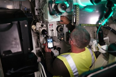 A Lockheed Martin engineer uses a mobile device with an advanced management information system to help perform maintenance inside a gunnery combat training simulator. Photo credit: Lockheed Martin