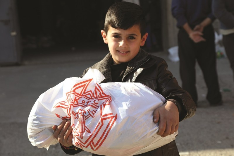 An Iraqi boy is glad to receive food stuffs provided by the Knights of Columbus. The Catholic fraternal organization has raised and committed almost $19 million in aid to Christians and other persecuted religious minorities in the Middle East.
