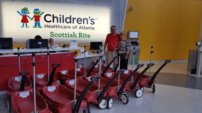 Roger Leggett stands next to customized Radio Flyer wagons with affixed IV poles that were donated to Children's Healthcare of Atlanta on behalf of his nonprofit organization, Chad's Bracket.
