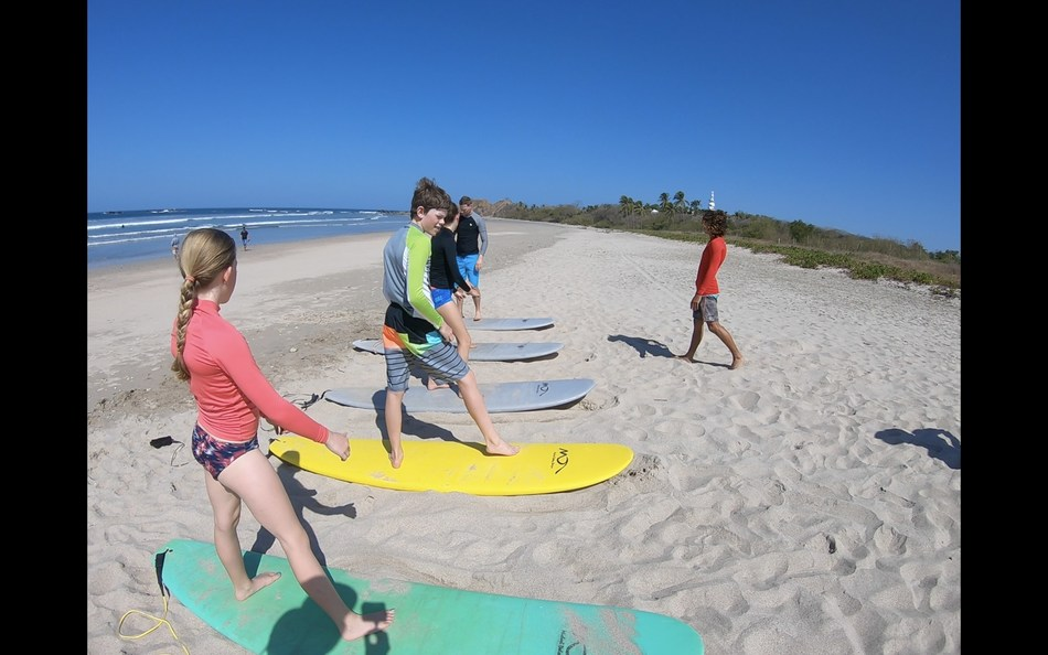 Surf Club students learn the basics on land before hitting the waves.