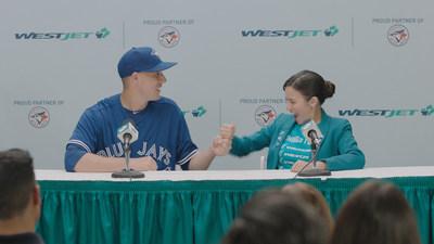 WestJet a lancé aujourd'hui une nouvelle série de publicités télévisées mettant en vedette le lanceur, Aaron Sanchez, le commentateur sportif à la télévision pour les Blue Jays de Toronto, Buck Martinez, et Marci, une superfan de WestJet. (Groupe CNW/WESTJET, an Alberta Partnership)