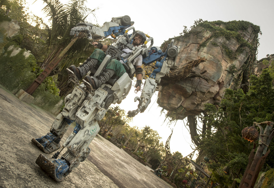 "Pandora Utility Suit Debuts at Disney's Animal Kingdom- A towering mechanical suit is sure to stop Walt Disney World Resort guests in their tracks when it debuts April 22 at Pandora - The World of Avatar at Disney's Animal Kingdom in Lake Buena Vista Fla. The new Pandora Utility Suit is inspired by the iconic Amplified Mobility Platform (AMP) suits of power armor from the epic film, ""AVATAR."" Perched ten feet high, a human pilot straps into the cockpit of this exo-carrier and controls its powerful, yet agile movements. Designed for restoration, this suit will traverse the land daily while its pilot interacts with guests, sharing details about the land's otherworldly landscape and highlighting the importance of preserving nature. (Kent Phillips, photographer)"
