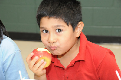 Tempe School District student enjoys local apples after receiving $180,000 grant that brings more healthy school meals to students. Photo taken by Amy Garza.