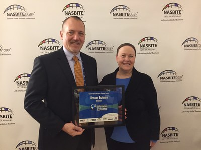 "Director of Government Relations for Brewer Science, Doyle Edwards, is presented with the ""Outstanding Missouri Exporter Award"" by International President of North America Small Business International Trade Educators, Tammy Marquez-Oldham."