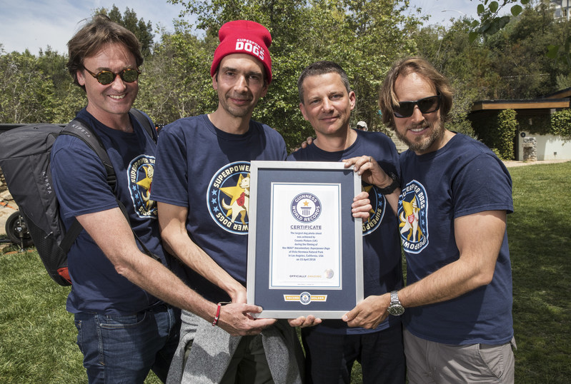 "Dominic Cunningham-Reid, Producer; Taran Davies, Producer; George Duffield, Producer; Daniel Ferguson, Writer, Director accept the GUINNESS WORLD RECORD title for ""Largest dog photo shoot."""