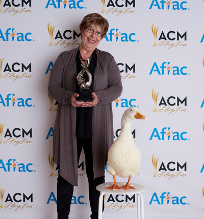 Aflac ACM Lifting Lives Honoree Judith Pinkerton poses with the Aflac Duck and her trophy.