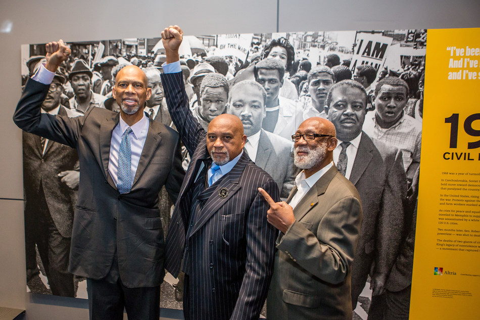 """Dr. Tommie Smith (center) and Dr. John Carlos (right) both accepted Newseum Free Expression Awards for their protest on the medal podium at the 1968 Summer Olympics. Before the award ceremony they posed in front of the Newseum's """"1968: Civil Rights at 50"""" exhibit, which includes the famous photo that captured their protest. Kareem Abdul-Jabbar (left), retired professional basketball player for the Milwaukee Bucks and the Los Angeles Lakers presented the award. Credit: Kea Dupree Photography"""
