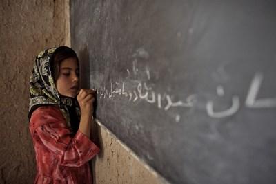 Une jeune fille écrit des lettres dari sur le tableau, dans une mosquée qui sert d'école communautaire à Kamar Kalagh, un village dans les environs de la ville d'Herat, en Afghanistan. © UNICEF/UNI118304/Noorani (Groupe CNW/Plan International Canada)