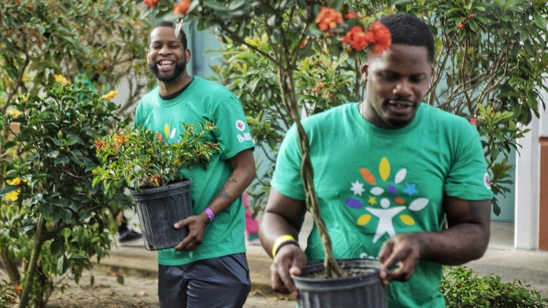 At the Comcast Cares Day project at Belvedere Elementary School in West Palm Beach, volunteers Michael Jean-Mary and Brandon McCray from the Wounded Veterans Relief Fund plant new trees.