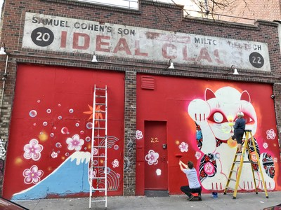 """Located on 22 E. 2nd Avenue in the Lower East Side, a neighborhood historically known as a hub for art and creation, the Ideal Glass mural has featured some of the most prolific artists of our time. Here, SAAB artists Ayakamay and Henry Quinson work to finish """"Catastophe"""", Japanese-American Ayakamay's iconic interpretation of the maneki-neko the Japanese cat figure which is often believed to bring good luck to the owner. Photo © SAAB Projects."""