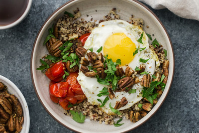 Spiced pecans are combined with hearty quinoa and roasted grape tomatoes and then topped with a fried egg for a flavorful and vegetarian-friendly breakfast bowl.