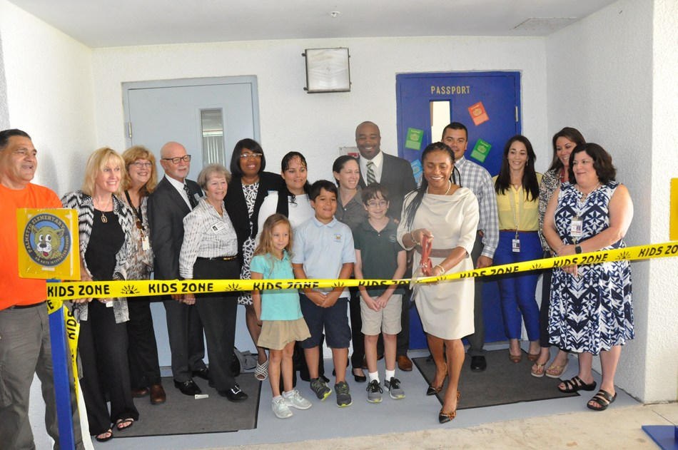 Palmetto Elementary School Principal Mrs. Gladys E. Harris cuts the ceremonial ribbon to formally open the school's new Carson Reading Room. The new reading room for students of the Elementary school was made possible by a Financial Grant from the BallenIsles Charities Foundation.