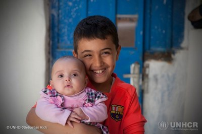 Mohammed's eldest son Emad holding his little sister Sajeda (PRNewsfoto/Zakat)