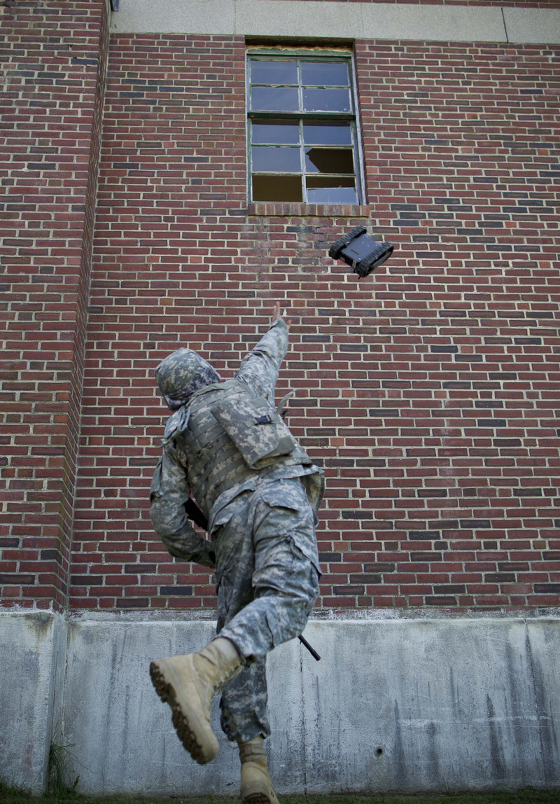 A U.S. soldier throws Endeavor Robotics' FirstLook robot through a second story window.