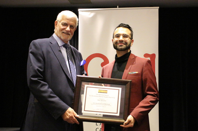 Omar Mouallem (à droite) reçoit son prix Mindset du président du Forum, Cliff Lonsdale, lors du gala des prix du CAJ à Toronto. (Groupe CNW/Le Forum du journalisme canadien sur la violence et le traumatisme)