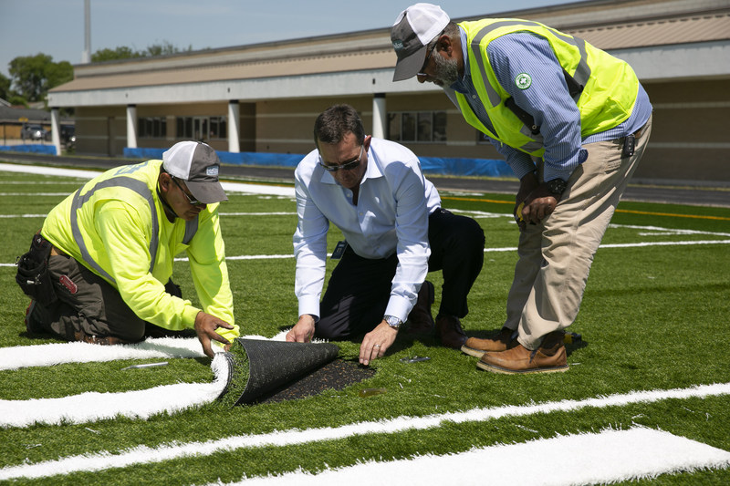 Reed J. Seaton, president and CEO of Hellas Construction, works with Salvador Martinez and Superintendent Saleh Khan to inlay yardage numbers on a Hellas Matrix® Helix field with Cushdrain® pad being installed at Dement Field in Galena Park, Texas today. Seaton is a 2018 finalist for the Entrepreneur Of The Year in the Central Texas Region.