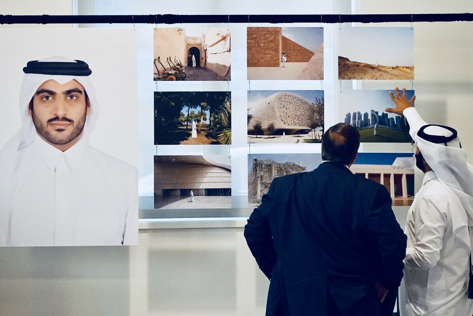 "Qatari photographer Khalid Al Hammadi discusses his work with a guest at the opening reception of ""Ruwad"" in Washington, DC. (Photo credit: Albert Ting)"