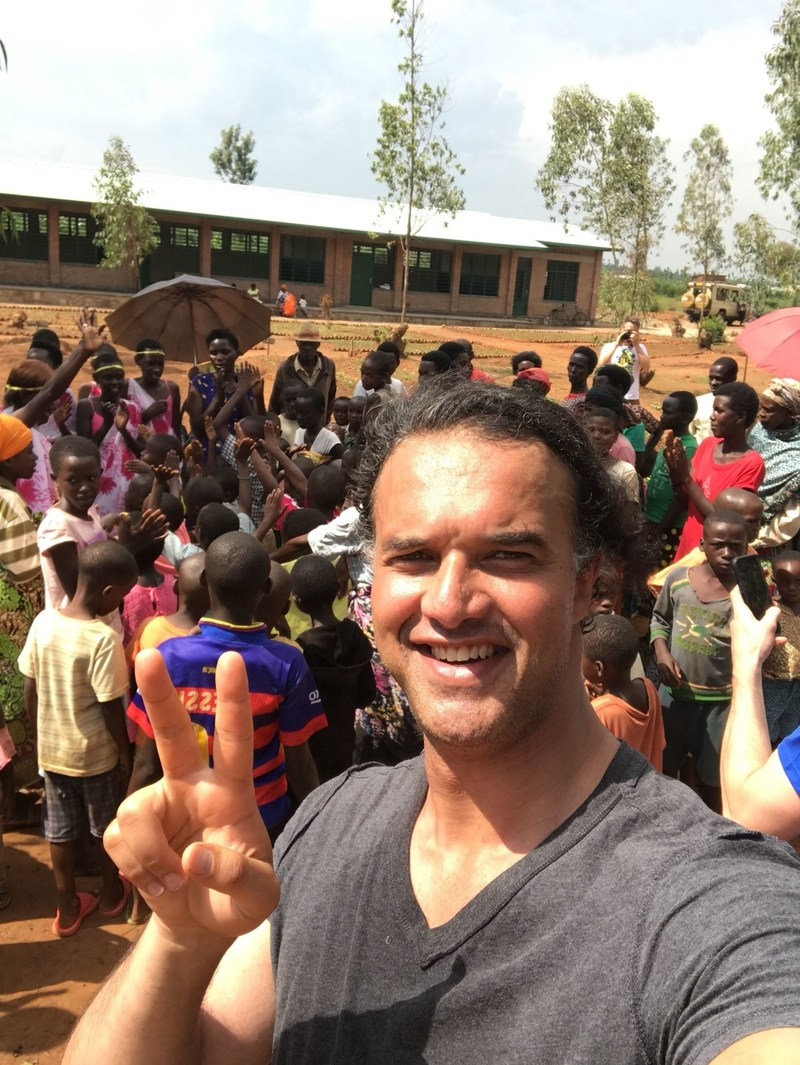 Paxful CEO Ray Youssef stands in front of a nursery school in Rwanda that his company helped build by donating $50,000 in bitcoin.