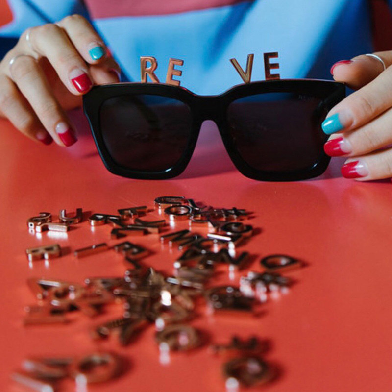The Alphabet Bar sunglasses include a magnetic strip that lines the top ridge of the frame to hold the gold-coated alphabets and symbol (A to Z, #).