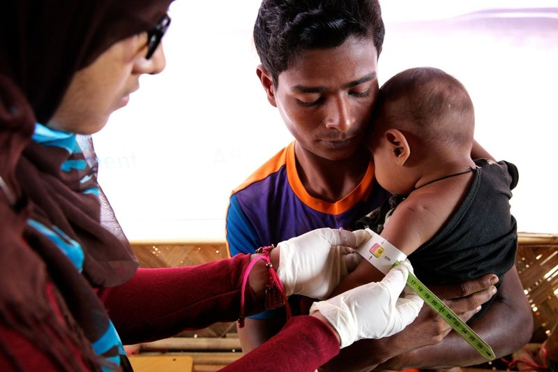 A health worker examines a Rohingya refugee child with a mid-upper arm circumference (MUAC) band to determine the child's nutritional status, at an Outpatient Therapeutic Feeding Programme (OTP) center at Unchiprang makeshift settlement in Teknaf, Cox's Bazar, Bangladesh, Tuesday 2 January 2018. © UNICEF/UN0158174/Sujan (CNW Group/UNICEF Canada)