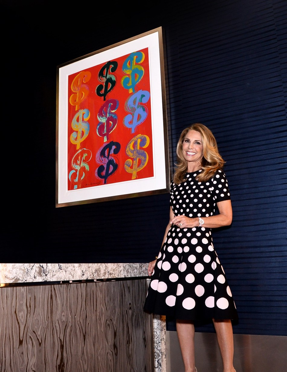 Suzi Cordish standing next to Andy Warhol's '$9: One Plate, one of the 40+ pieces in The Cordish Art Collection that Mrs. Cordish carefully curated for the flagship luxury Live! Hotel.