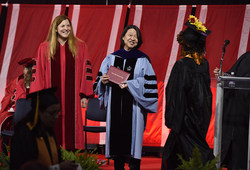 Massachusetts Secretary of Labor and Workforce Development Rosalin Acosta assists Bunker Hill Community College President Pam Eddinger with conferring Class of 2018 degree and certificates at College's 44th Commencement Ceremony