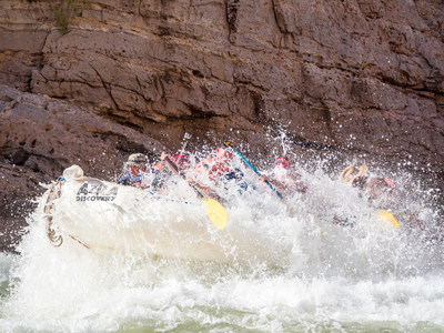 A previous Raytheon-No Barriers Grand Canyon Veteran Wilderness Expedition team battles the Colorado River rapids.