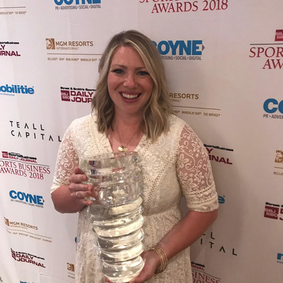 Phoenix Suns fan Whitney Collins poses with the Best in Mobile Fan Experience trophy won by 15 Seconds of Fame at the 2018 Sports Business Awards in New York City.