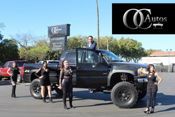 OC Autos management team posts with black pickup truck on dealership lot