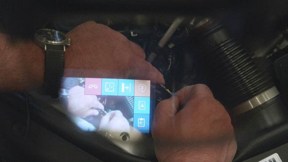 Tech Live Look - Computer menu visible to on-site technician wearing smartglasses while working on engine.
