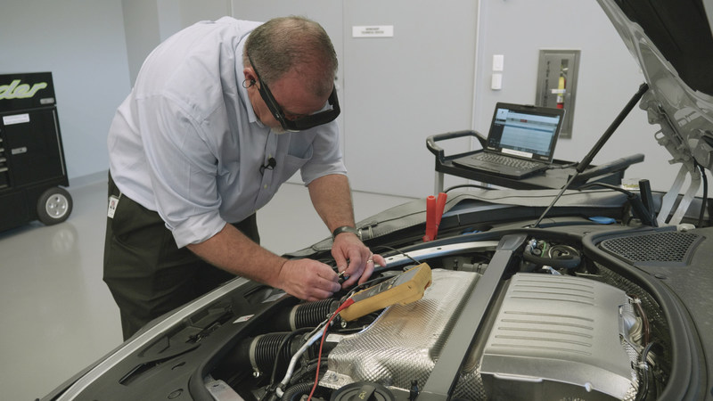 Tech Live Look - On-site technician works on engine while interacting with remote expert via smartglasses.