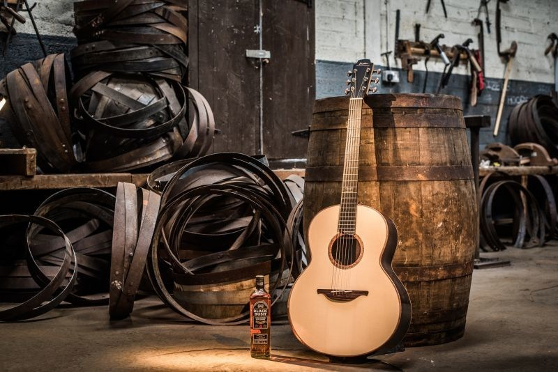 Bushmills® Irish Whiskey and Lowden Guitars have joined forces to create the first guitar using pot still copper from The Old Bushmills Distillery: the Bushmills x Lowden Black Bush Edition. Pictured is the new guitar and BUSHMILLS BLACK BUSH at The Old Bushmills Distillery. (PRNewsfoto/Bushmills Irish Whiskey)