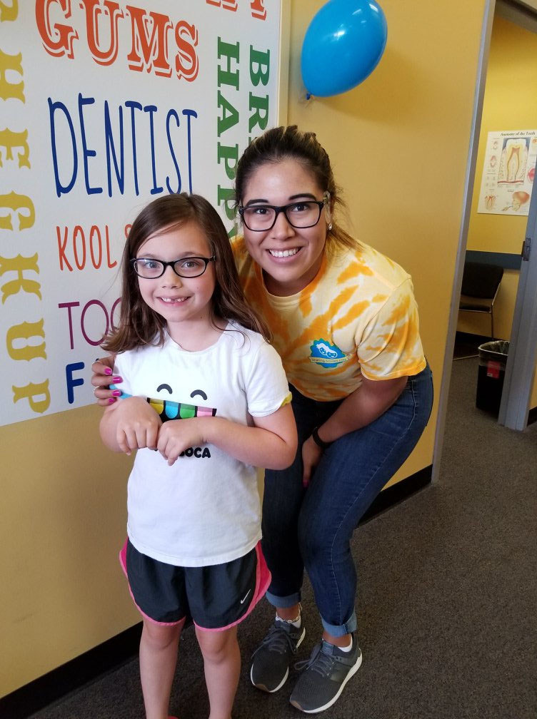 A child and volunteer staff member from Kool Smiles were all smiles during their annual free care day.