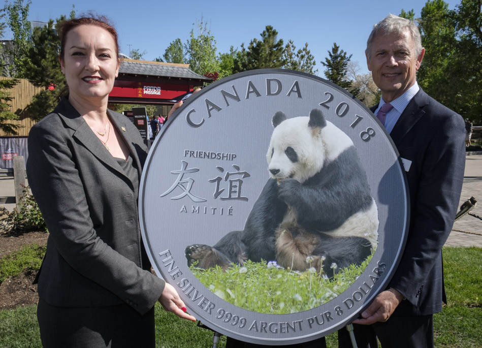 """From the left : Francine Hochereau, vice-president, marketing and communications at the Royal Canadian Mint and Greg Royer, chief operating officer at the Calgary Zoo unveil the fine silver coin """"The Peaceful Panda: a Gift of Friendship"""" (CNW Group/Royal Canadian Mint)"""