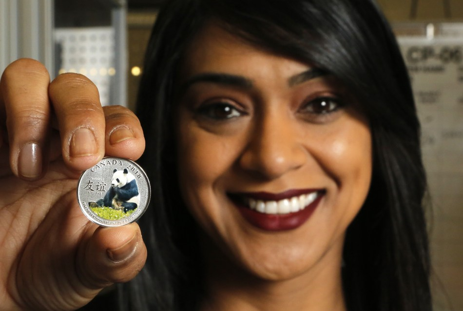 """Minister of Small Business and Tourism Bardish Chagger holds the fine silver coin """"The Peaceful Panda: a Gift of Friendship"""" after participating in a ceremonial coin strike at the Royal Canadian Mint on Friday in Ottawa. This year marks the Canada-China Year of Tourism (CNW Group/Royal Canadian Mint)"""