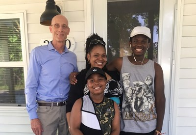 Adient's Russ Burgei, vice president of engineering, presents the Van Hoose family with their new home.