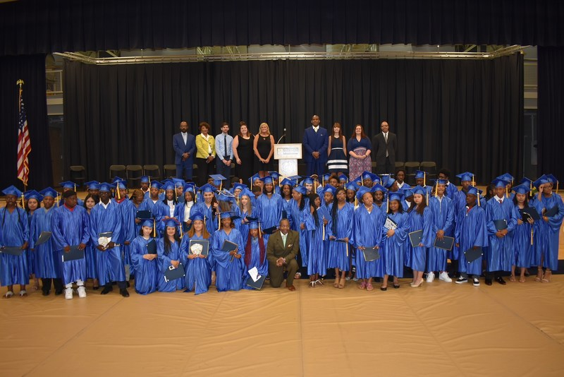 Chester Mayor Thaddeus Kirkland (front row, center) shown with eighth-grade graduates of Chester Community Charter School, at commencement ceremonies held at Neumann University, after presenting the commencement address to the students. Also shown, at top, are school administrators and faculty members, including Dr. David Clark, chief education officer(far left); Dr. Linda Portlock (second from left), deputy superintendent; and Terrane Polnitz, Aston Campus Principal(fourth from right).