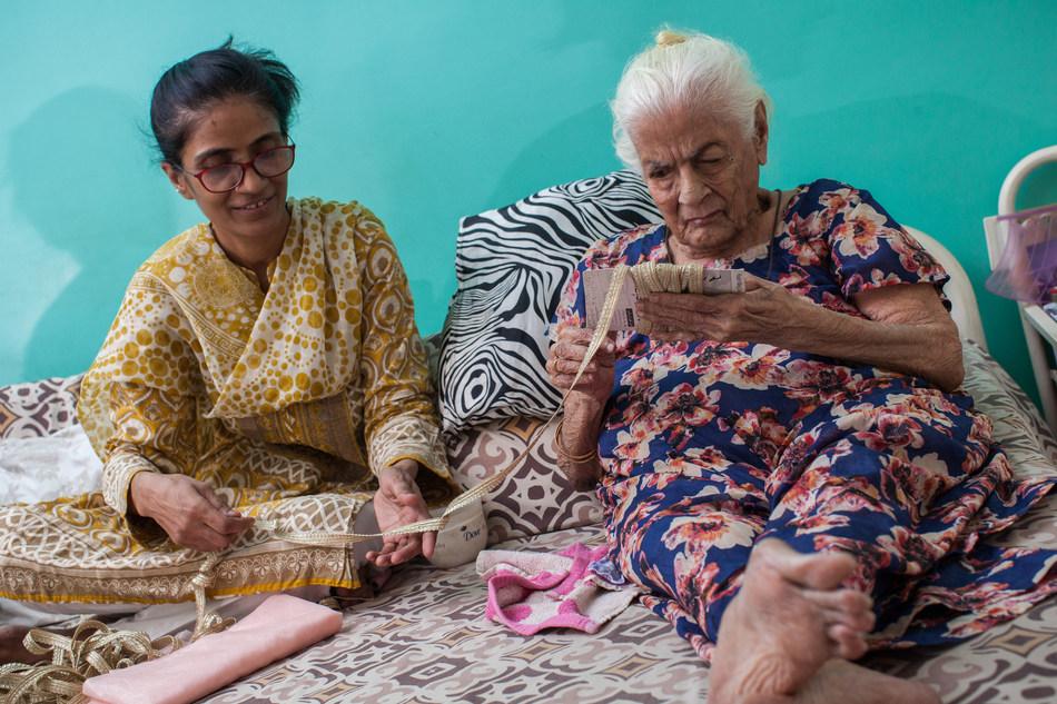 Karachi, Pakistan : Mehrunnisa Iqbal Vertejee affirme qu'il est important qu'elle prenne soin de sa belle-mère, Sherbanoo Vertejee, 86 ans, pour enseigner à ses enfants à respecter les personnes plus âgées. Crédit : Asim Hafeez pour Orb Media.