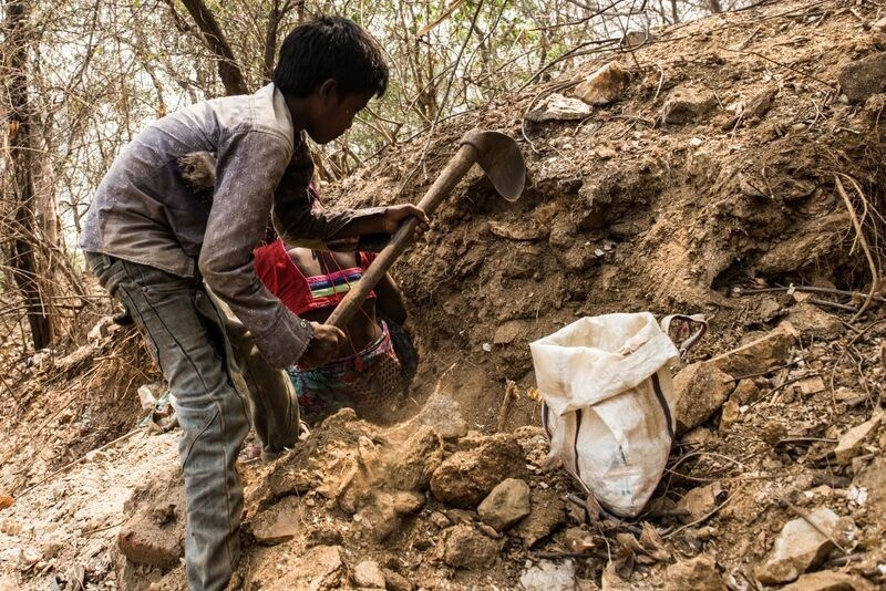 """""""If I can, I would definetely go to school. But I have to work here to earn,"""" says ten-year old Pavan, as he cracks a chunk of earth using his spade and pulls it down. Pavan, his eight-year-old brother Kumar and their mother immediately get busy digging through the rubble to pick mica flakes. Photo/World Vision India (CNW Group/World Vision Canada)"""