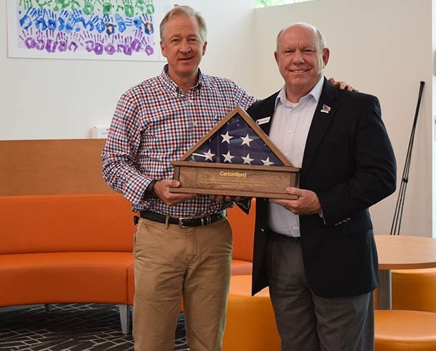 Mark Rayfield, President/CEO of CertainTeed, was presented with the flag that flew during the Key Ceremony of the 250th home completed by Homes For Our Troops (HFOT). The flag was presented by HFOT President Brigadier General (Retired) Tom Landwermeyer.