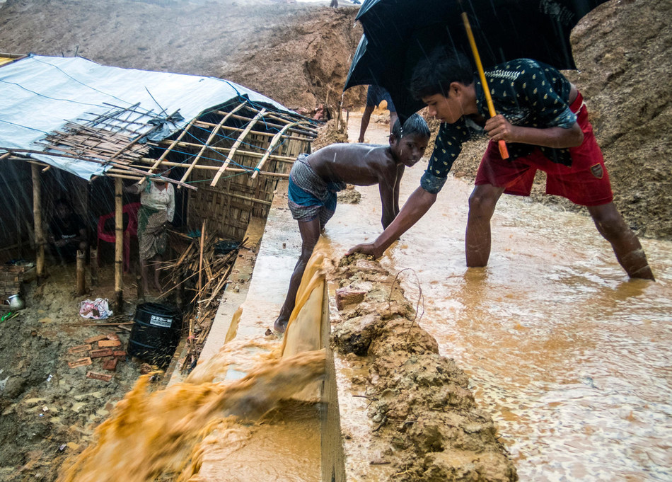 On 10 June 2018 in Bangladesh, Rohingya refugee children struggle with the mud collecting on a retaining wall during the first days of monsoon rain in Kutupalong Camp, Cox's Bazar. © UNICEF/UN0216986/LeMoyne (CNW Group/UNICEF Canada)