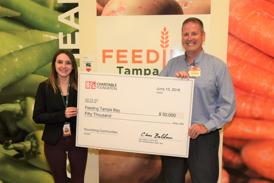 Darren Fredericks, general manager, BJ's Wholesale Club in Tampa (right) presents a $50,000 donation from the BJ's Charitable Foundation to Kat Agresta, procurement manager, Feeding Tampa Bay (left) to support their Hunger-Free Summer Programs.
