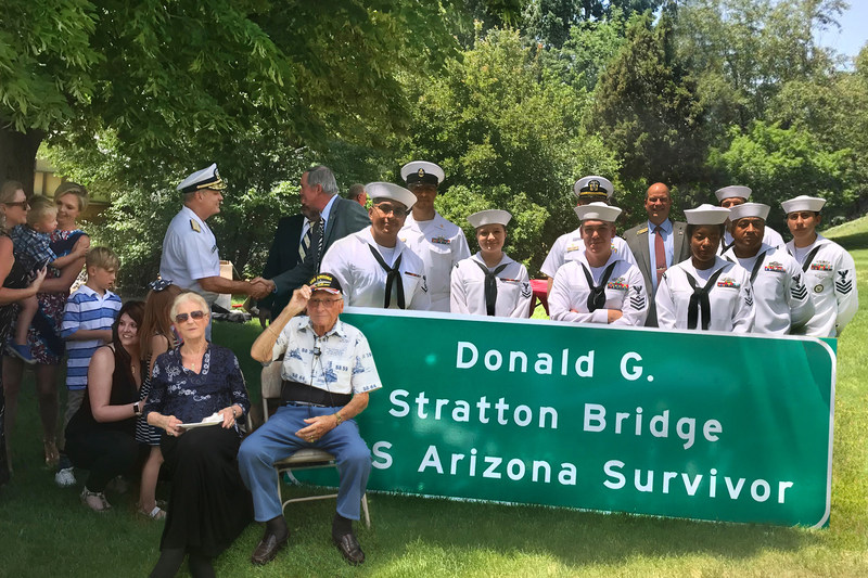 Don Stratton, survivor of Pearl Harbor's USS Arizona takes in the newly named Interstate 25 /Fillmore Bridge sign presented to him by the Pikes Peak Heroes Legacy Committee during a ceremonial dedication at Holiday Village in Colorado Springs. (Photo courtesy of Holiday Village)