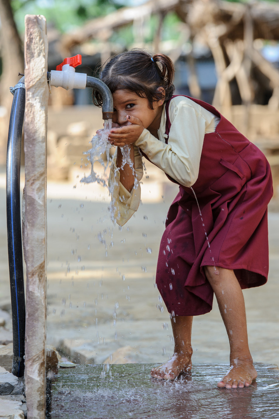 A young girl drinks clean water from a hand pump now available in Mahadev Pura village, Madhya Pradesh, India. Through a WaterAid project, all local homes now have toilets and handwashing is regularly practiced, greatly reducing the rate of illness, especially among women and children. (WaterAid/ James McCauley)