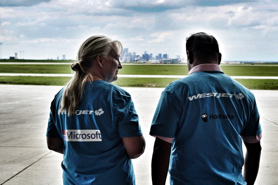#hackinthehangar attendees from Microsoft and HootSuite look out at the Calgary skyline from the WestJet hangar (CNW Group/WESTJET, an Alberta Partnership)