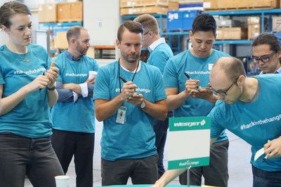 Hackathon participants working on ideas in WestJet hangar (CNW Group/WESTJET, an Alberta Partnership)