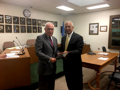 James Maida, GLI President.CEO, (right) presents Larry B. Eliason, Exec. Secretary for the South Dakota Commission on Gaming, with a commemorative plaque to mark GLI's 30th year of doing business with the Commission.